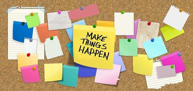 """tablón de anuncios de corcho con post it de colores y destaca uno en amarillo que pone """"make thing happen"""""""