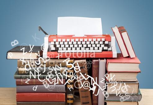 Maquina de escribir encima de torre de libros para redactar informe CESAG