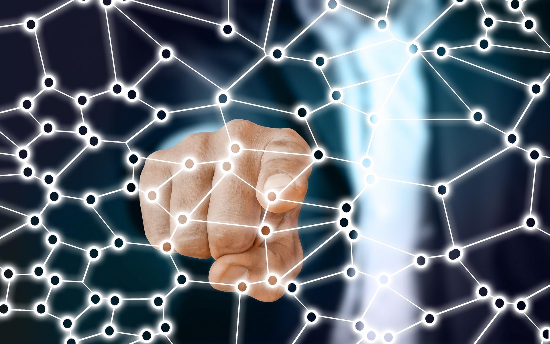 dedo señalando una red de puntos conectados, simil de los medios de comunicación